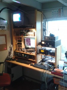 An average view of my ham radio shack: radio's, wires going arround, and the desk cluttered with homebrew and experiments.